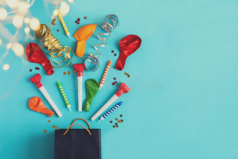 Collection of colorful birthday party objects in a gift box on blue paper background with defocused light. Holiday celebration stock images