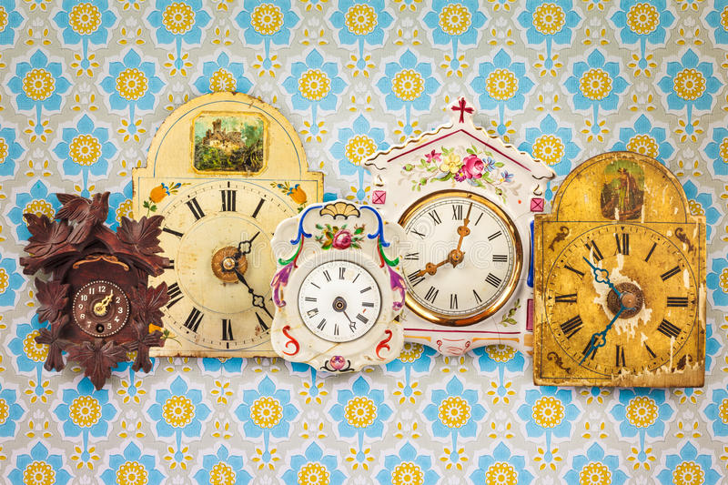 Collection of colorful hanging clocks in front of retro wallpaper stock photo