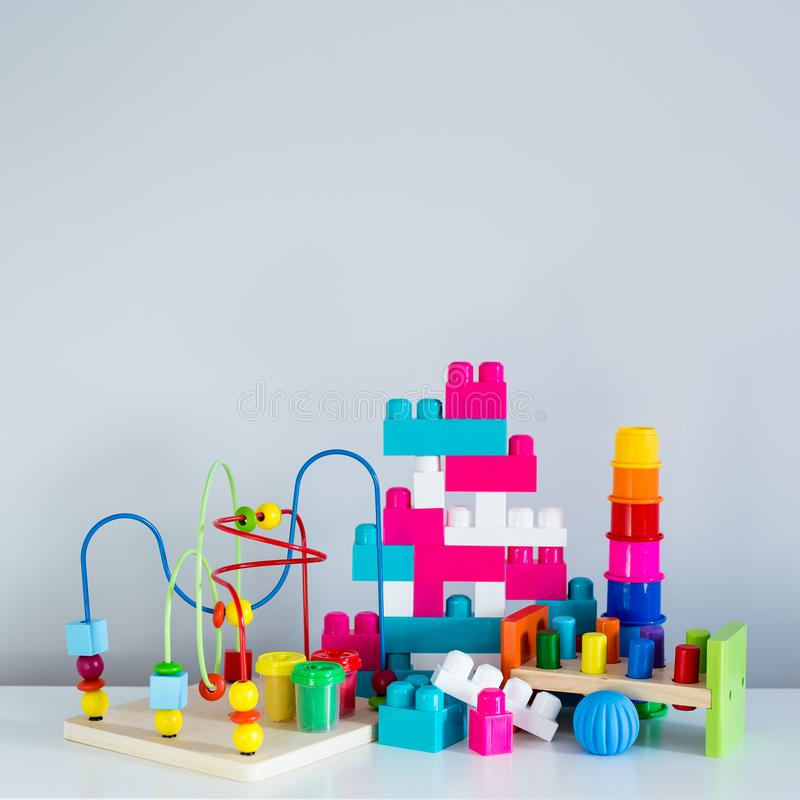 Collection of colorful toys and constructor bricks over white wall. Background stock photography