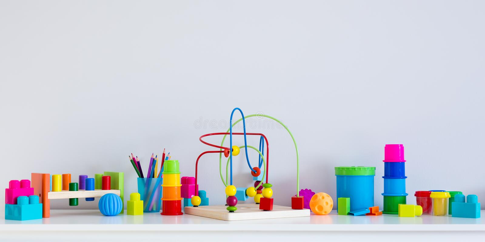 Collection of colorful toys and copy space over white wall. Background stock photography