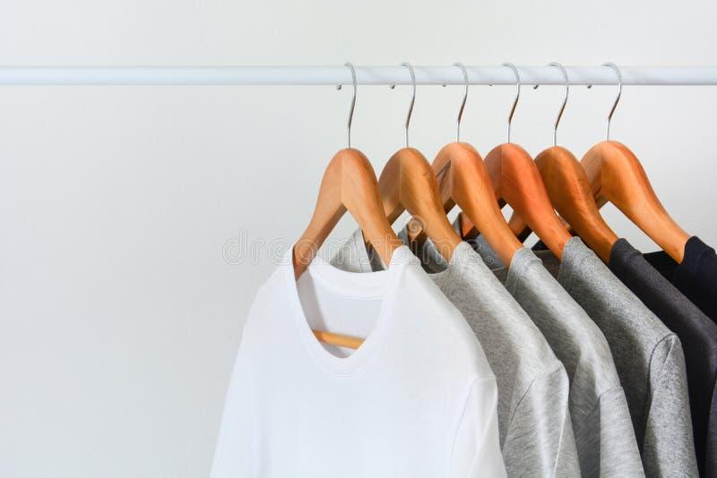 Collection de couleur noire, grise et blanche accrochant sur le cintre en bois dans le support de cabinet ou d'habillement images stock