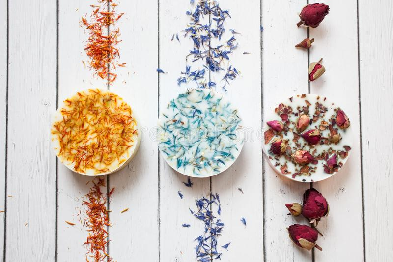 Collection de savon fait main avec les fleurs sèches de la rose, du bleuet et du calendula sur un fond en bois blanc images stock