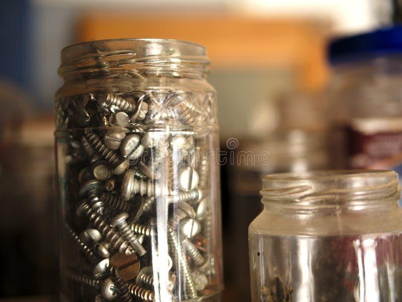 Collection de vis et de matériel dans le pot en verre se reposant sur le banc d'outil photo libre de droits