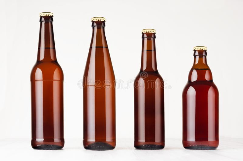 Collection different brown beer bottles, mockup. Template for advertising, design, branding identity on white wood table. Collection different brown beer stock photography