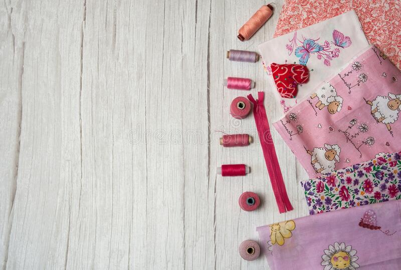 A collection of fabrics in different shades of pink, reels of thread and pins on a light wooden background. Free time. I love sewing. A collection of fabrics in royalty free stock photography