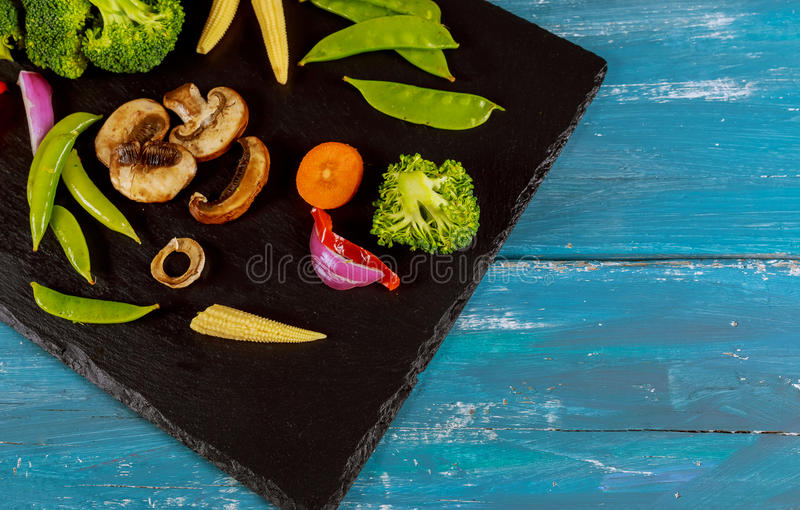 Collection fresh green vegetables placed on black stone royalty free stock photo