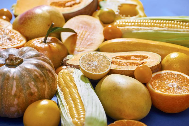 Collection of fresh yellow fruit and vegetables on the blue background.  royalty free stock photos