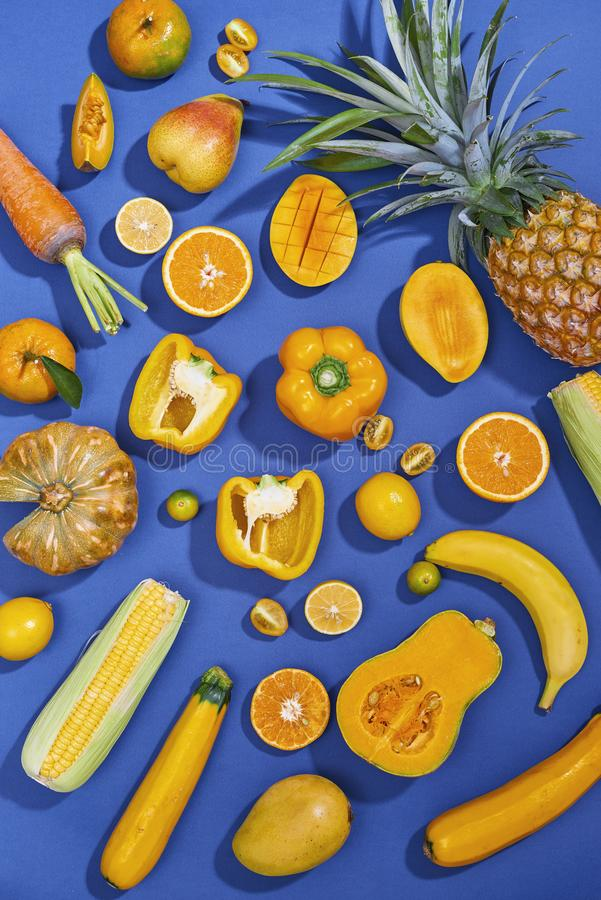 Collection of fresh yellow fruit and vegetables on the blue background.  royalty free stock images