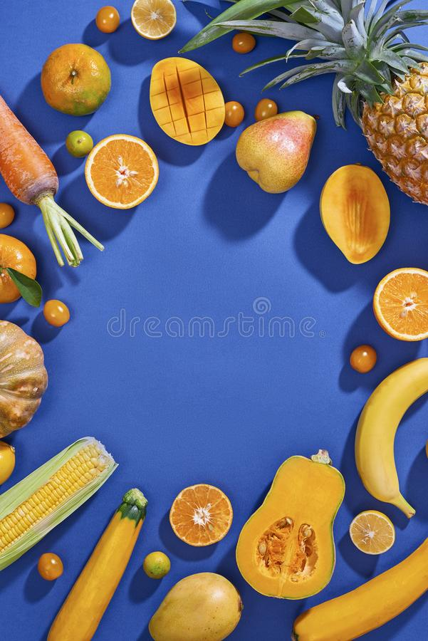 Collection of fresh yellow fruit and vegetables on the blue background stock photography