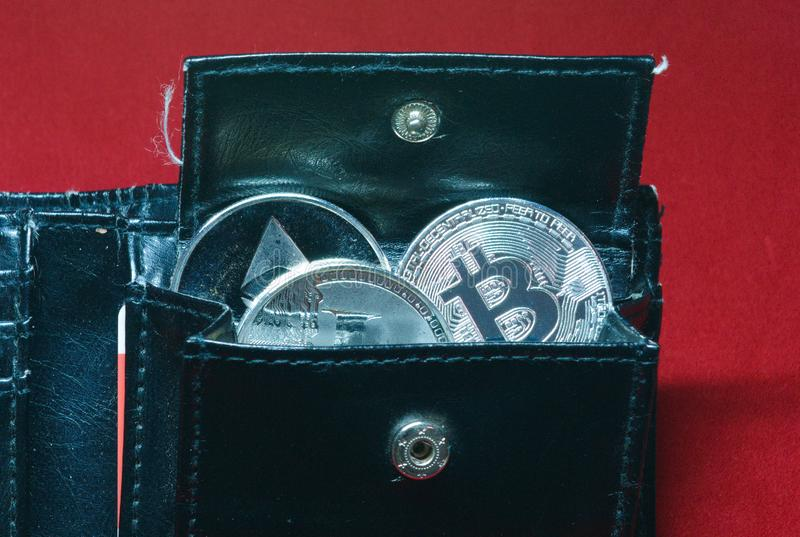 A collection of gold and silver cryptocurrency coins in a wallet royalty free stock image