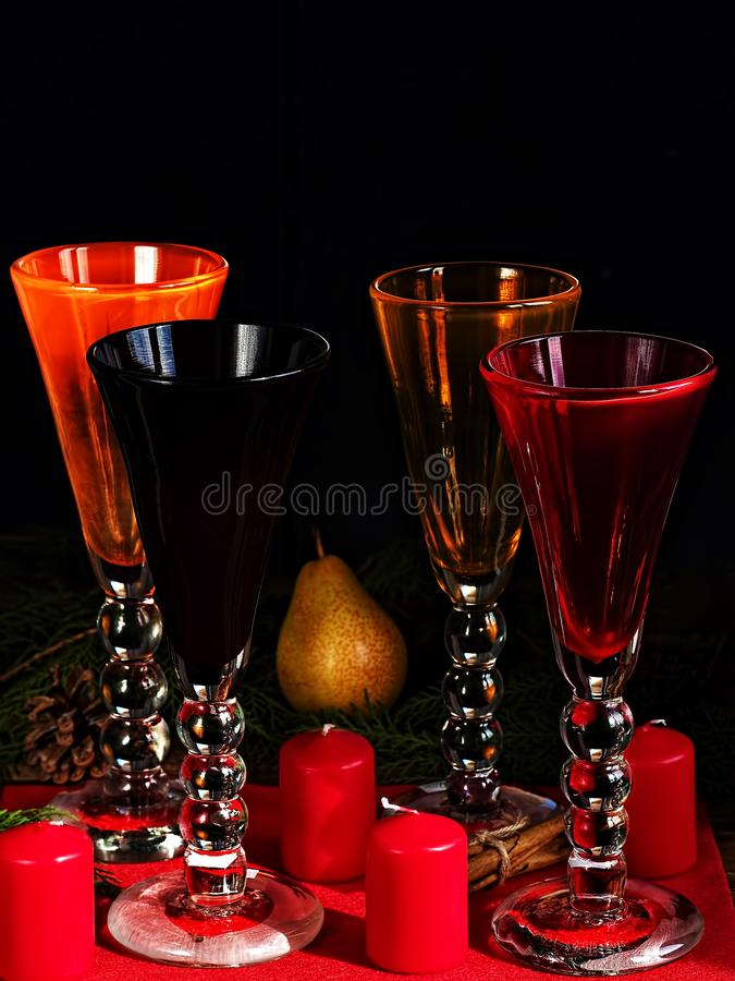 Collection of handmade colored glass goblets on black background. Cinnamon sticks, four candles and a pear on a red napkin. Close- royalty free stock images