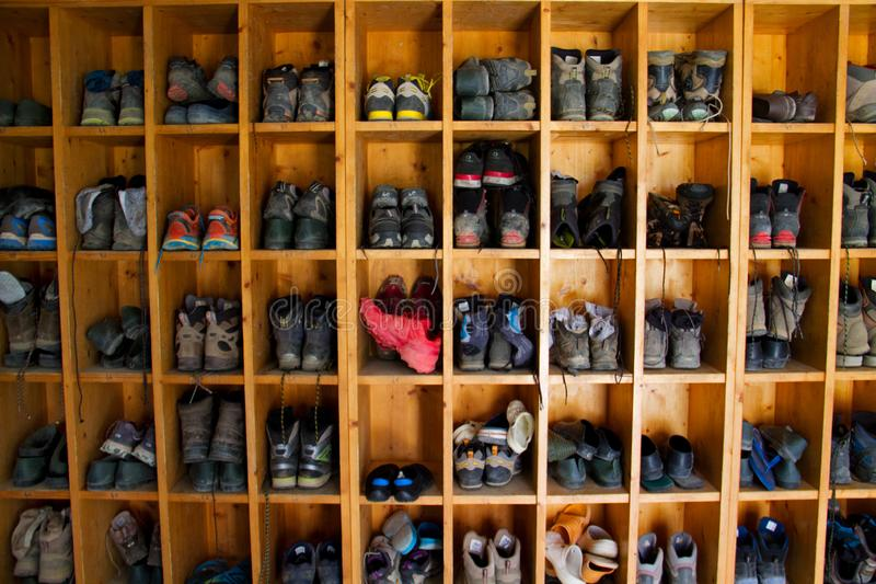 Hiking boots on shelves in mountain hut. Collection of hiking boots in a mountain cabin in the Pyrenees stock photos
