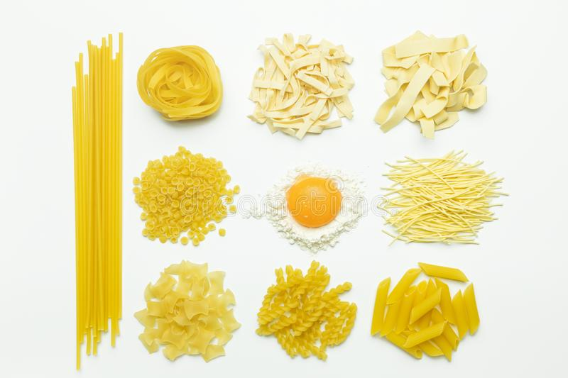 Collection of italian pasta, flour and chicken egg isolated top view. Collection of italian pasta, flour and chicken egg isolated top view on white background royalty free stock photo