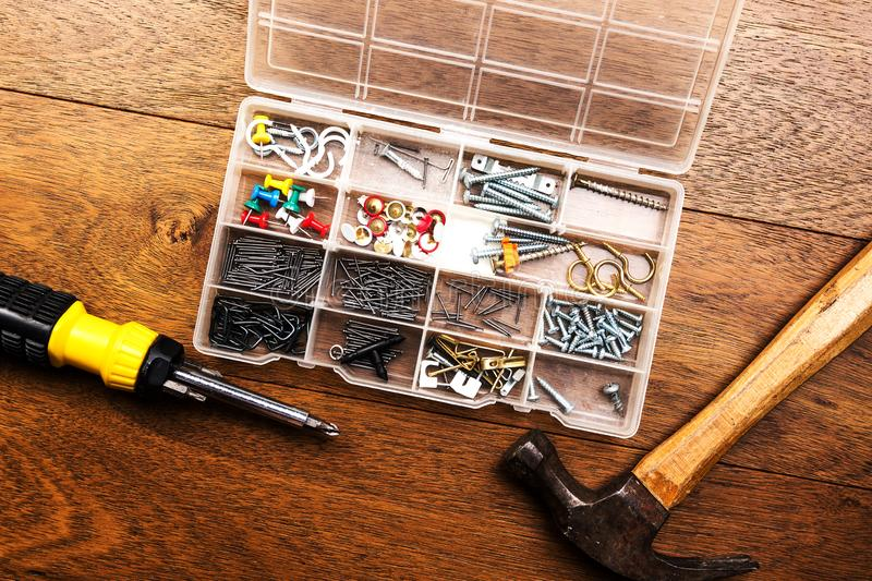 Collection of nails, thumb nails, screws, hooks, pins, hanger, plastic and bolts in plastic box next to a hammer and a screwdriver. On wooden background stock photography