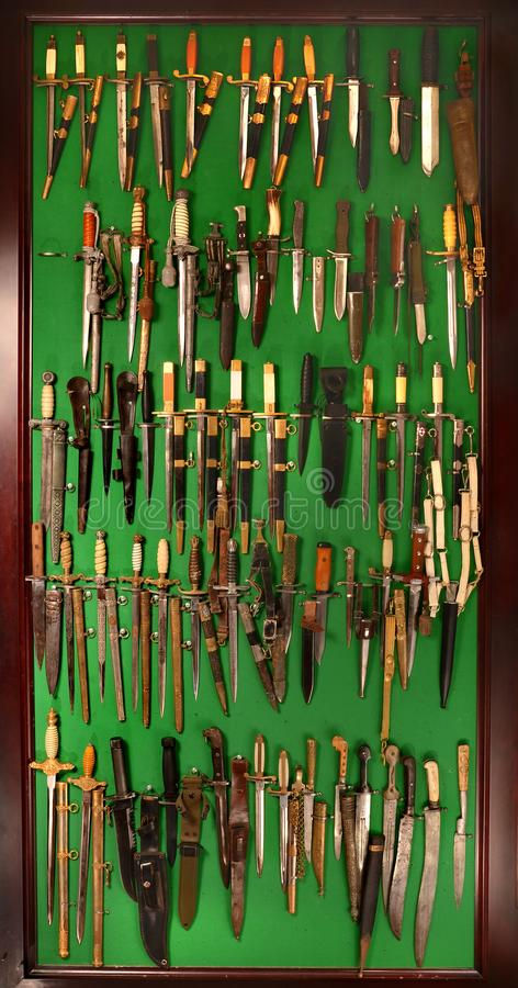 Collection of old edged weapons, knives, daggers, dirks stock images