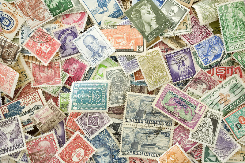 Collection of old expired international stamps. A pile of canceled stamps from different countries stock photography