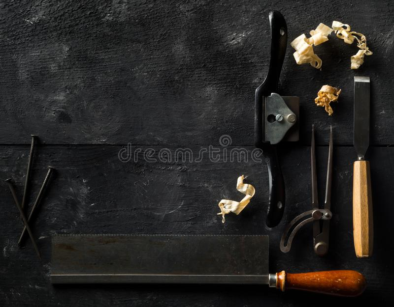 Collection of old, used wood working tools flat lay from above on black wooden background with copy space - repair, craftsmanship stock image