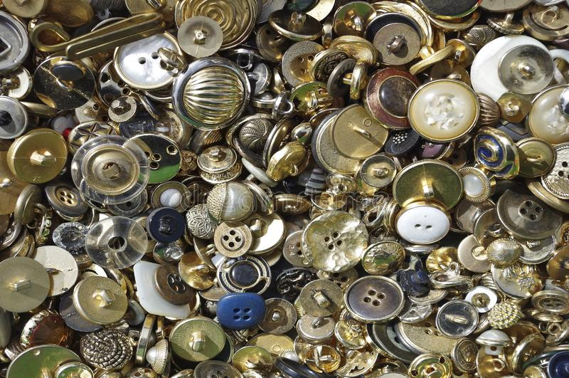 Flea market buttons. Collection overview of older brass buttons in varied sizes and shapes used for clothing. garments textiles closure attatchment assortment stock photo