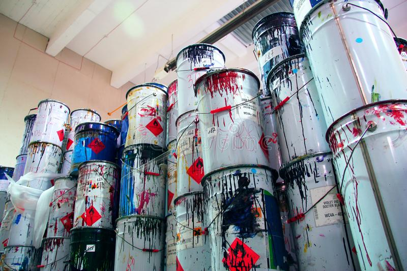 A collection of paint cans, glue buckets, mastic and toxic and hazardous material stacked. View from below stock images