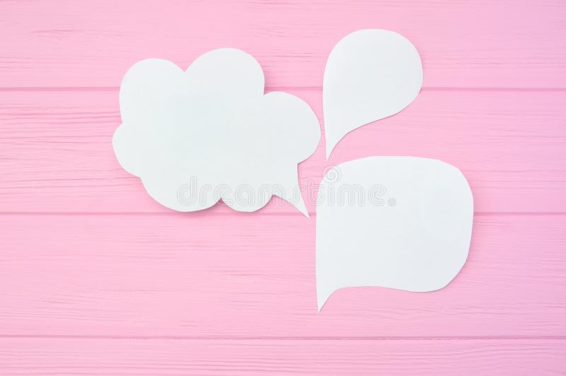 Collection paper speech bubble. Dialog questions and answer on a pink wooden background royalty free stock photos