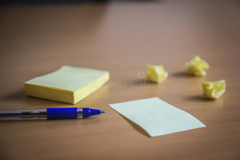 Collection of pins and note paper bunch and loose papers on wooden board. ball point pen. side view ready to fill your text and de royalty free stock images