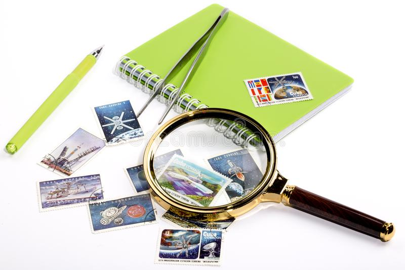 Collection of postage stamps. With a magnifying glass and a notebook with a pen royalty free stock images