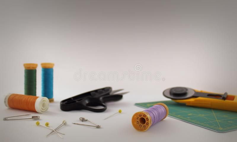 Collection of quilting sewing equipment tools on a light background with copy space. A photograph featuring a collection of quilting sewing tools including royalty free stock photography
