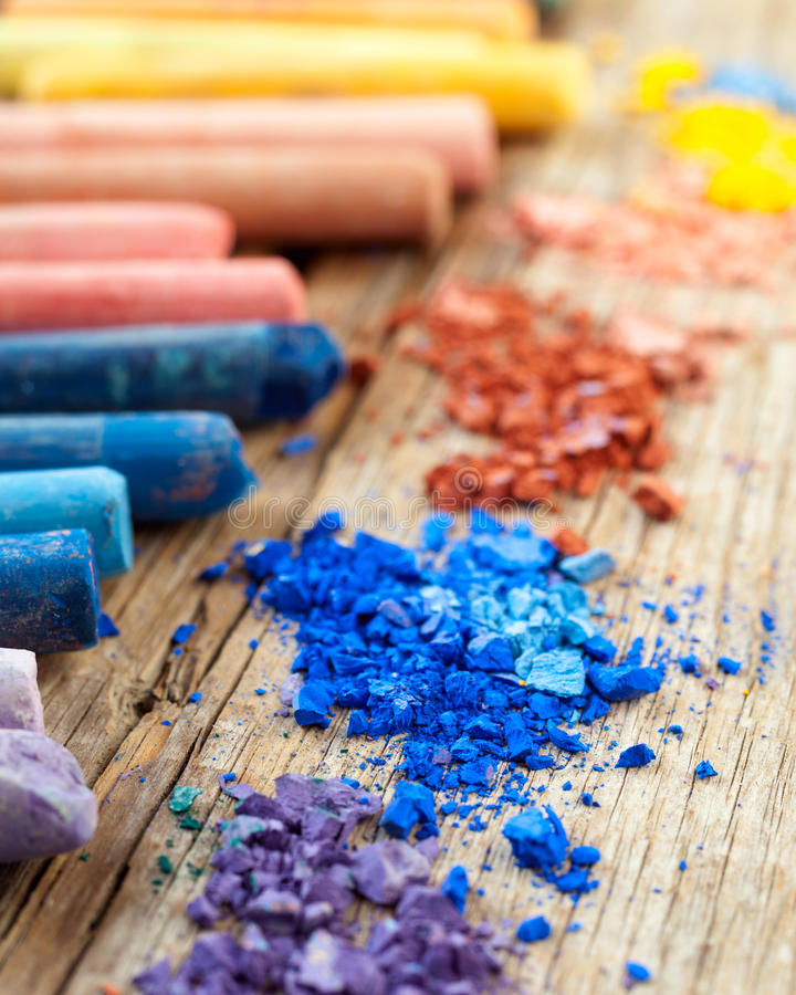 Collection of rainbow colored pastel crayons with crushed chalk. royalty free stock photo