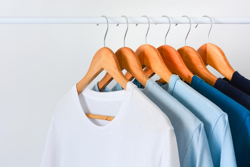Collection shade of blue tone color t-shirts hanging on wooden clothes hanger in closet royalty free stock image