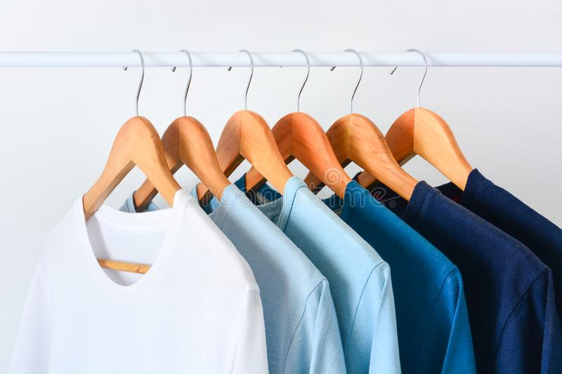 Collection shade of blue tone color t-shirts hanging on wooden clothes hanger on clothing rack. Close up collection shade of blue tone color t-shirts hanging on royalty free stock photo