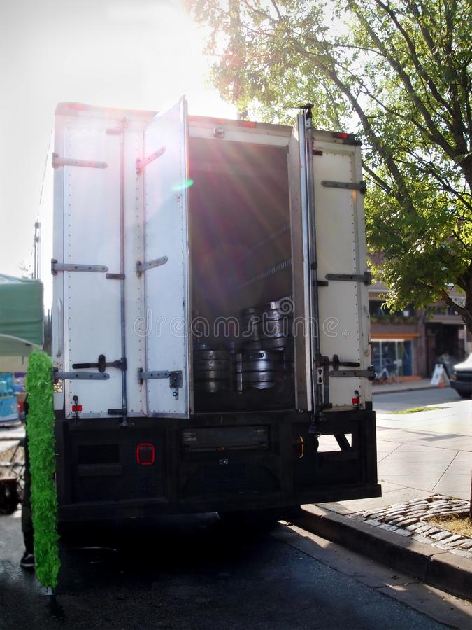 Big Kegs in Box Truck. A collection of silver beer kegs piled together in the back of an open truck parked at a city curb with late afternoon sunbeams streaming stock image