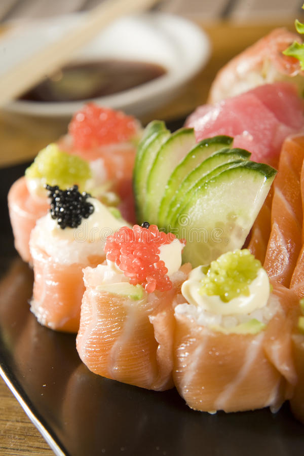 Collection of sushi and sashimi. Salmon roll sushi with caviar, cucumber and tuna sashimi on a plate with soy sauce and chopsticks in the background stock photos