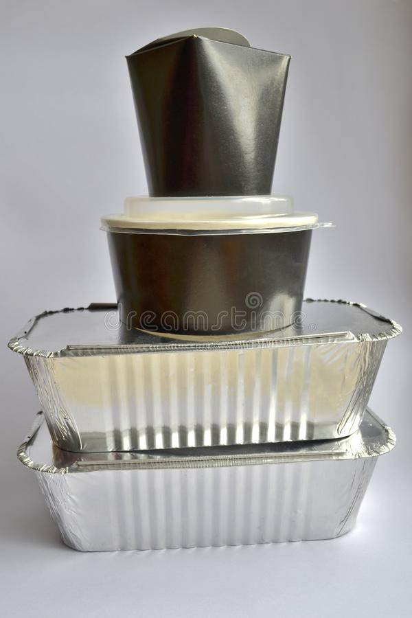 Collection of take away foil boxes for a food. Foil and cardboard containers on white background, stand on each other royalty free stock photo