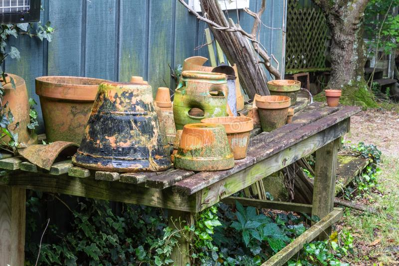 Collection of terra cotta pots on an open slat table. Horizontal aspect stock images