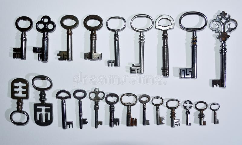 Twenty two Antique keys on a white Background stock images