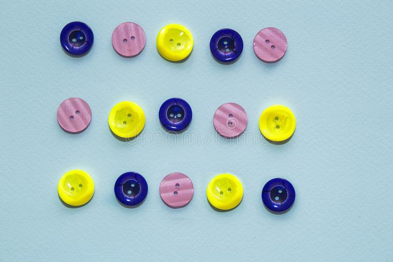Collection of various multicolored sewing button on blue background. Yellow, purple, dark blue buttons. Sewing stock images