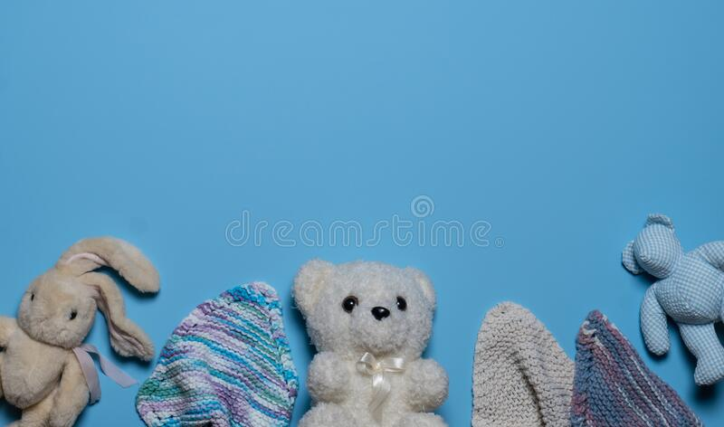 A collection of vintage stuffed bear and bunny animals and baby bath washcloths on a light blue background. Flat lay, copy space royalty free stock photos