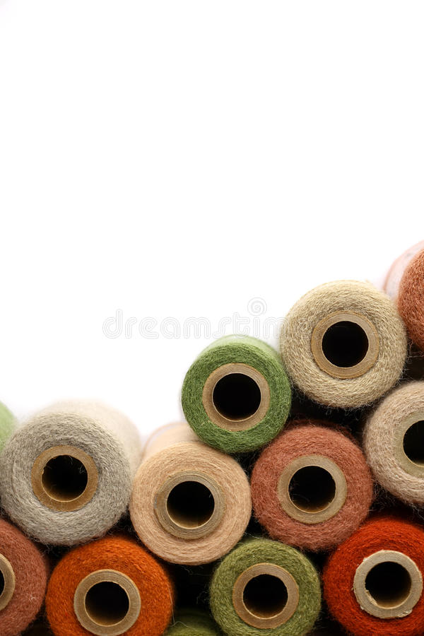 Collection of Vintage Yarn Spools Frame White Background. A collection of natural colored, vintage yarn spools frame the corner of a white background royalty free stock photography