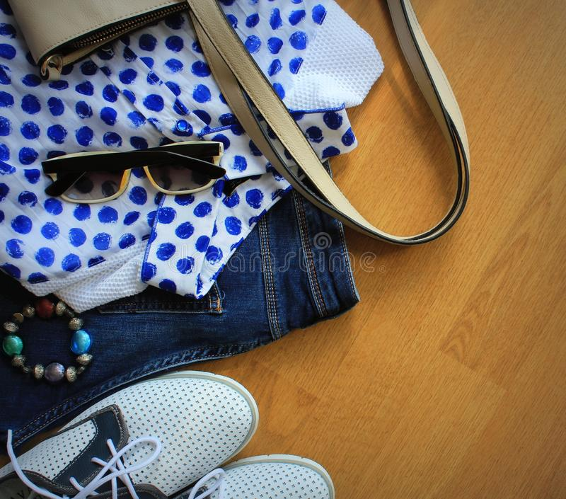 Collection of women`s clothes. Jeans, shoes, bluose, glass. Top view stock images