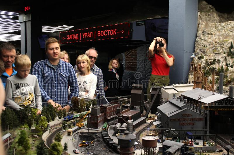 An employee of the museum takes pictures of visitors. Collective image of cities and regions of the Russian Federation, made in miniature. National show-museum royalty free stock images