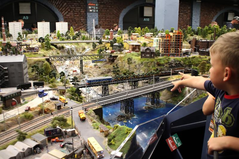 Children watch the moving train. Collective image of cities and regions of the Russian Federation, made in miniature. National show-museum `Grand layout Russia royalty free stock image