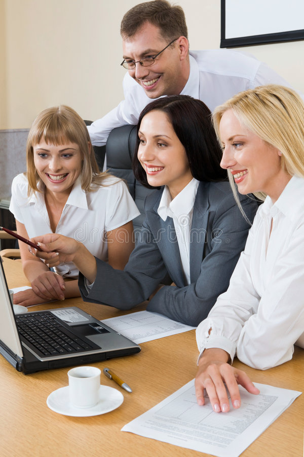 Collective job. Portrait of young businesswoman showing to the monitor of laptop and three businesspeople gathered together around the table with the laptop royalty free stock photography