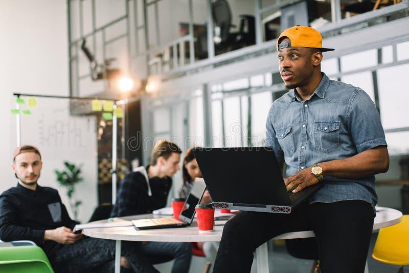 Collega afroamericano pelato buio in camicia dei jeans e cappuccio e computer portatile gialli usando in ufficio moderno multirac immagini stock
