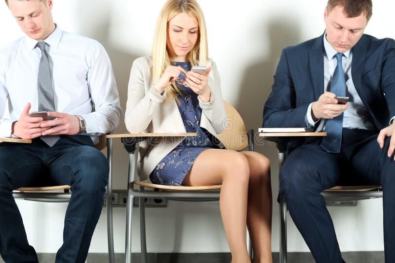 Collega di affari che si siede sulle sedie e che per mezzo del telefono cellulare fotografie stock