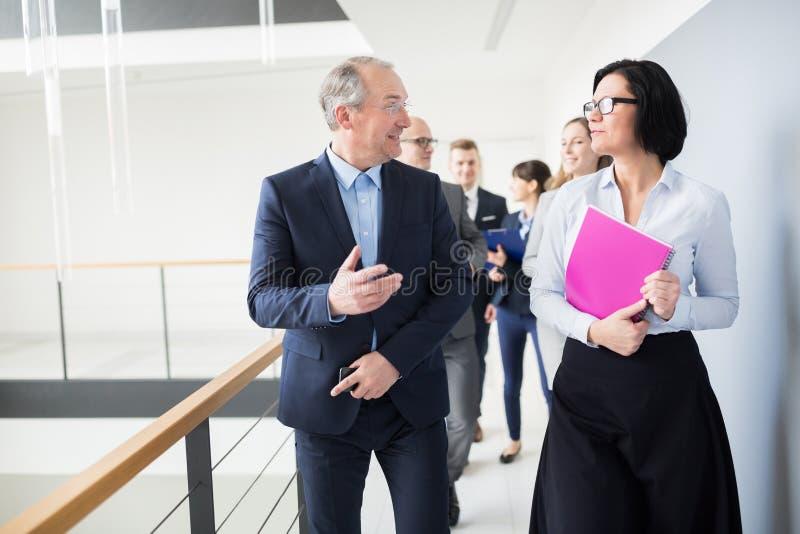 Collega di Communicating With Female dell'uomo d'affari mentre camminando sopra immagine stock libera da diritti