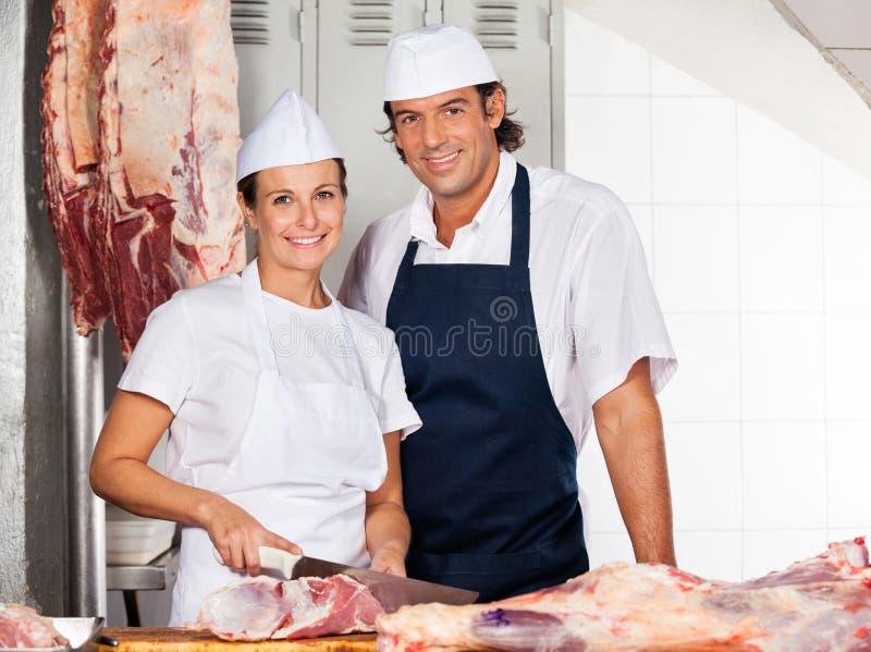 Collega di Cutting Meat By del macellaio in negozio immagini stock