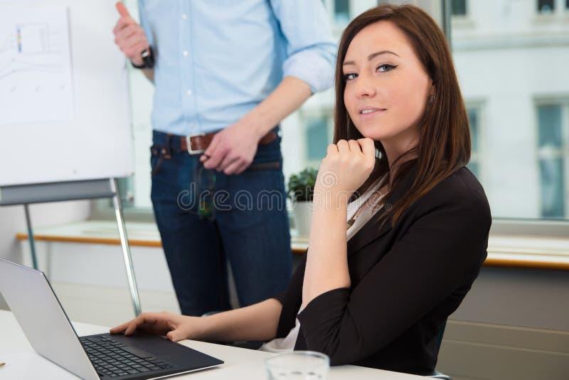 Collega di Using Laptop While della donna di affari che dà presentazione fotografia stock libera da diritti