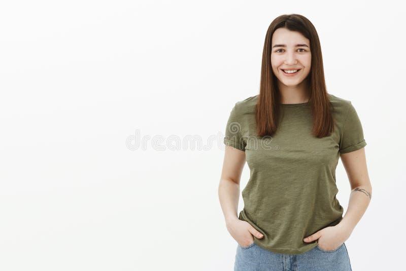 Collega femminile sveglio con lo sguardo fisso ambizioso che si tiene per mano in tasche che aspettano assegnazione, sorridenti l fotografie stock