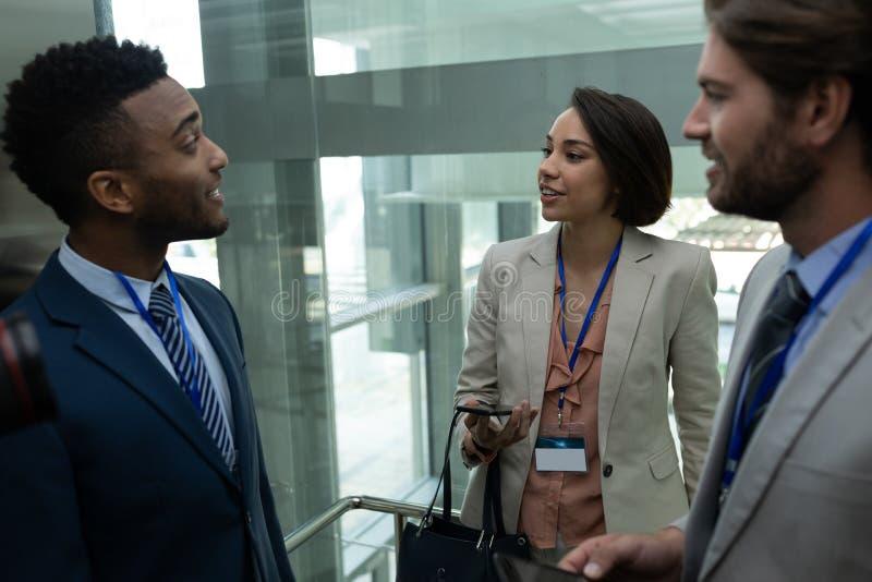 collega Multi-etnico di affari che interagisce a vicenda nell'elevatore fotografia stock