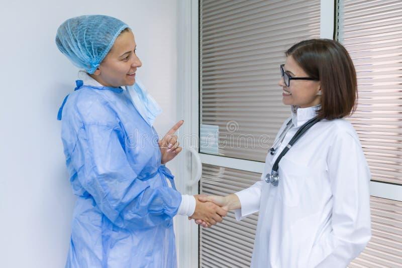 Collega's artsen chirurgische arts en therapeut die in het ziekenhuis spreken stock foto's